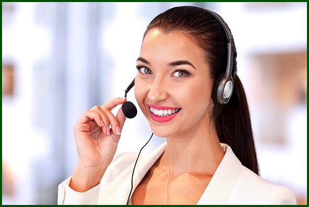 Young smiling female call center worker with headset.