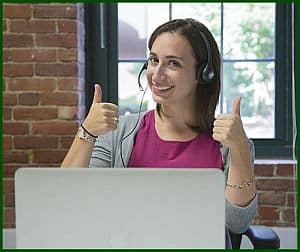 Salesperson giving 2 thumbs up in front of her computer.