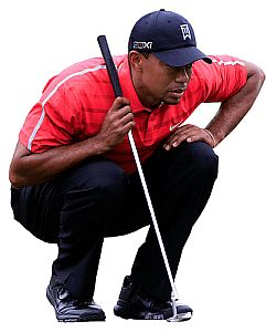Tiger Woods concentrating on lining up a putt.