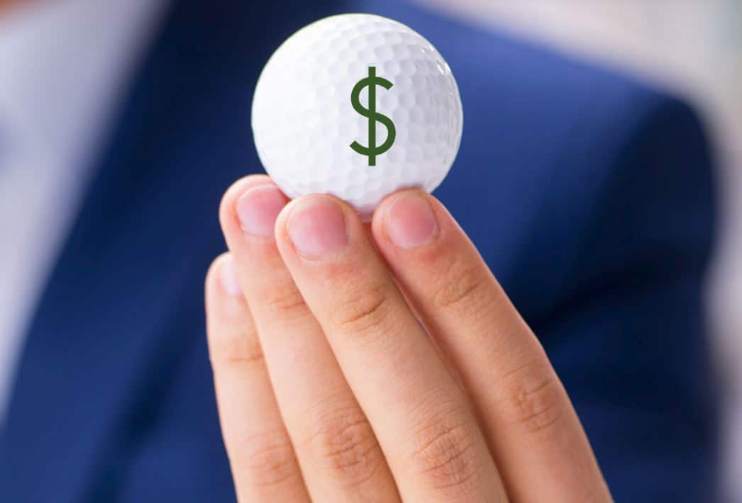 Salesperson's hand holding golf ball with $ sign on it