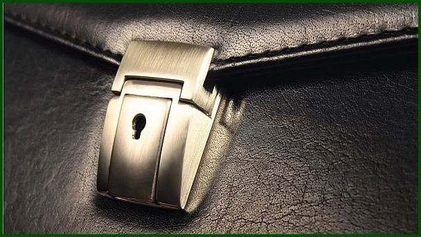 Image of a closed metal lock on a leather case.