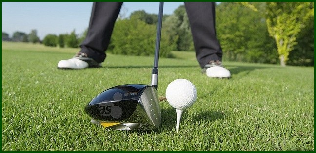 Golf ball on tee with driver poised to hit it